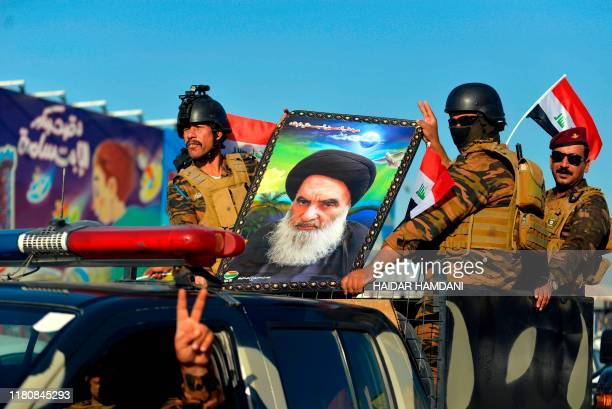 Iraqi security forces ride with a picture of Shiite cleric Grand Ayatollah Ali al-Sistani in the central holy shrine city of Najaf on November 8 ,...