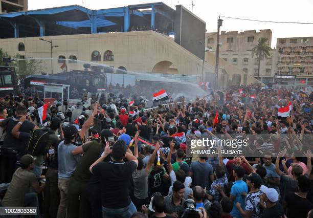 Iraqi security forces spray water cannon at protesters waving national flags during clashes at a demonstration against unemployment and a lack of...