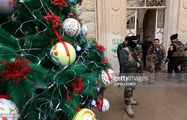 Iraqi security forces stand guard as Christians attend a Christmas Eve service at the Mar Shimoni church in the town of Bartalla near Mosul on...