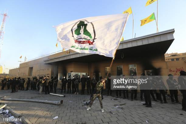 Iraqi security forces stand guard as outraged Iraqi protesters storm the US Embassy in Baghdad protesting Washington's attacks on armed battalions...