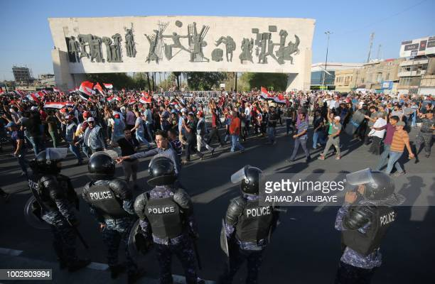 Iraqi security forces stand guard as protesters waving national flags during a demonstration against unemployment and a lack of basic services in the...