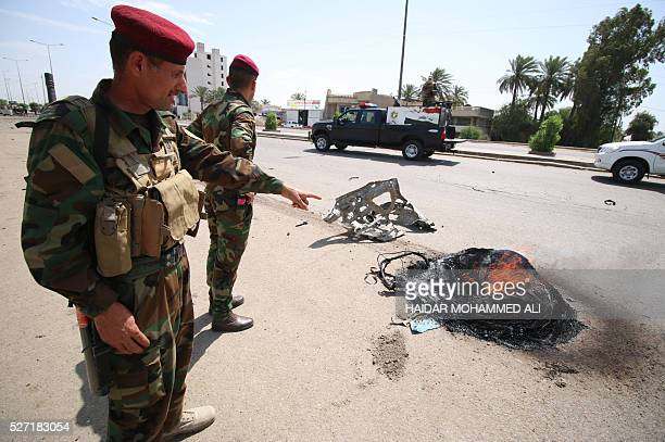 Iraqi security forces stand guard as they check the damage following a car bomb targeting Shiite pilgrims heading to commemorate the death of Imam...