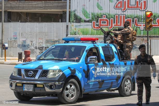 Iraqi security forces stand guard at a checkpoint enforcing a curfew due to the COVID-19 coronavirus pandemic during the Eid al-Fitr holiday which...