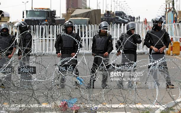 Iraqi security forces stand guard during a protest by supporters of Iraqi Shiite cleric Moqtada alSadr calling for governmental reform and...