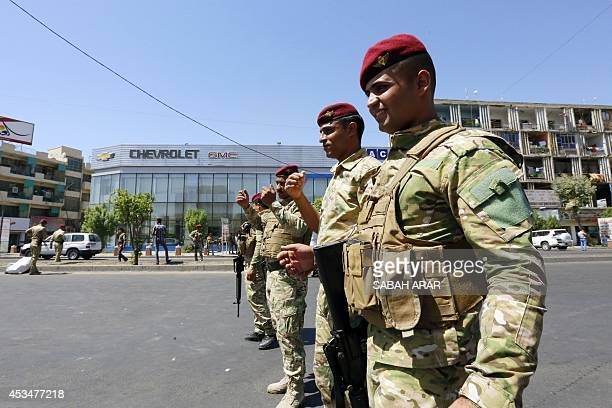 Iraqi security forces stand guard in a street in Baghdad's commercial district of Karrada on August 11 2014 as security measures have been reinforced...