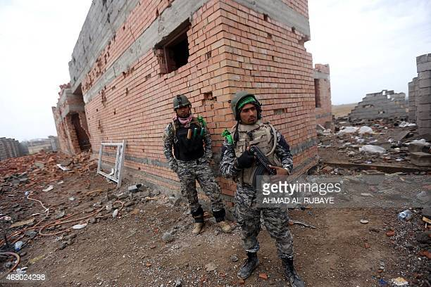 Iraqi security forces stand next a damaged house in the southern entrance of the city of Tikrit on March 29 2015 during a military operation to...