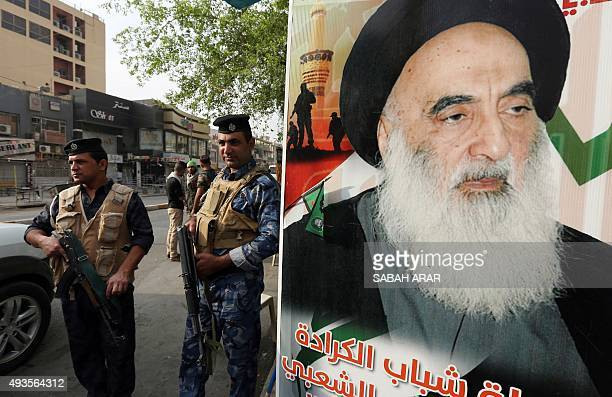 Iraqi security forces stand next to a poster of Grand Ayatollah Ali al-Sistani in Baghdad's Karada district on October 21, 2015 as Iraqi Shiites...