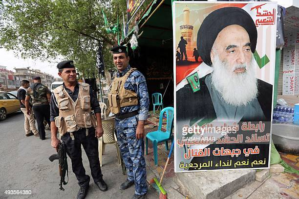 Iraqi security forces stand next to a poster of Grand Ayatollah Ali al-Sistani in Baghdad's Karada district on October 21, 2015 as Iraqi Shiite...