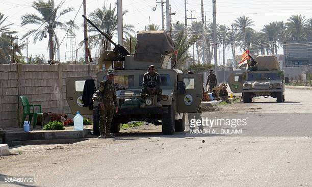 Iraqi security forces stand next to their vehicles as they clear alSajarya district on the eastern outskirts of Ramadi the capital of Anbar province...