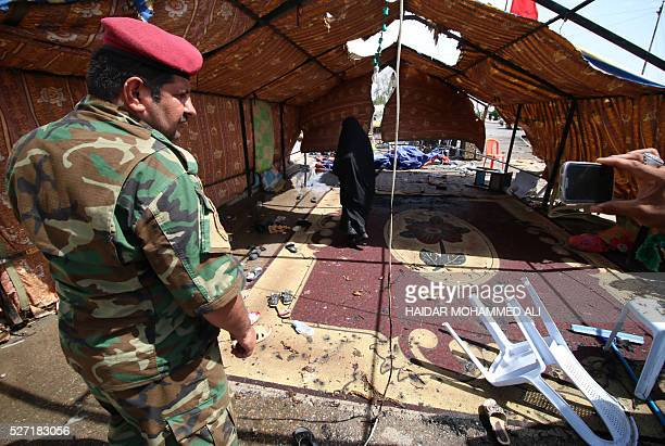 Iraqi security forces take a photo as a woman checks the damage following a car bomb targeting Shiite pilgrims heading to commemorate the death of...