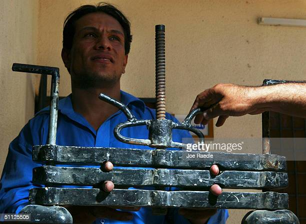 Iraqi security guard, Ayad Mutashar, shows off a finger vice that was one of the tools of torture that Saddam Hussein's slain son, Odai, is believed...