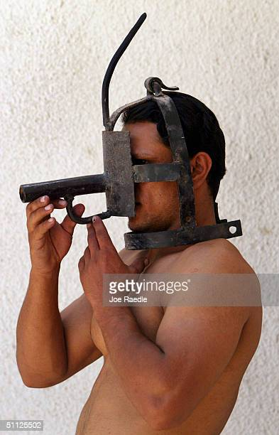 Iraqi security guard Ayad Mutashar shows off a mask that was one of the tools of torture that Saddam Hussein's slain son Odai is believed to have...