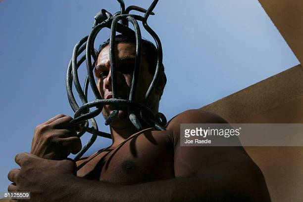 Iraqi security guard, Ayad Mutashar, shows off a mask that was one of the tools of torture that Saddam Hussein's slain son, Odai, is believed to have...