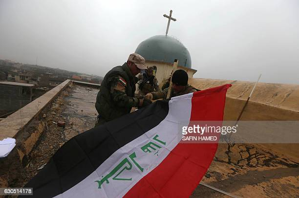 Iraqi security members stand guard and put up their country's national flag as Iraqi Christians attend a Christmas Eve service at the Saint John's...