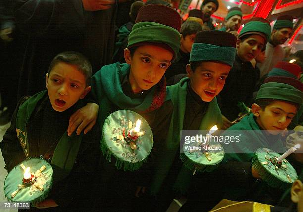 Iraqi Shi'ite boys hold burning candles during Ashura day celebrations the anniversary of the death of Imam Hussein grandson of Prophet Muhammad on...