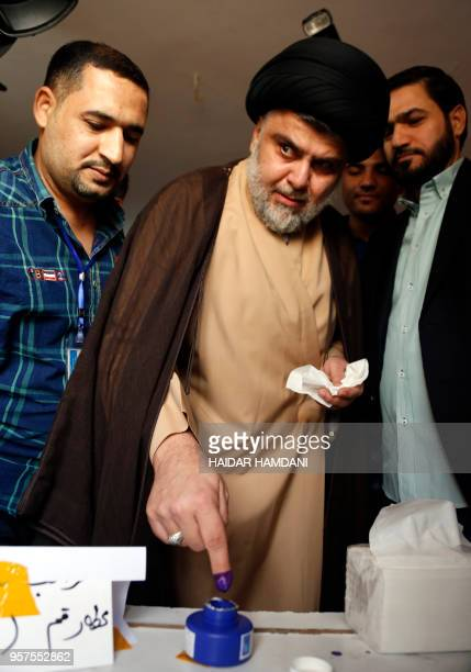 Iraqi Shiite cleric and leader Moqtada alSadr dips his index finger in ink inside a polling station in the central holy city of Najaf on May 12 2018...