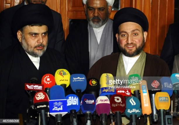 Iraqi Shiite cleric Moqtada al-Sadr and Iraqi Shiite Muslim leader Ammar al-Hakim speak during a meeting to discuss economic and security issues held...