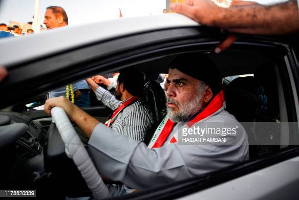Iraqi Shiite cleric Moqtada al-Sadr drives a car as he joins anti-government demonstrators gathering in the central holy city of Najaf on October 29,...