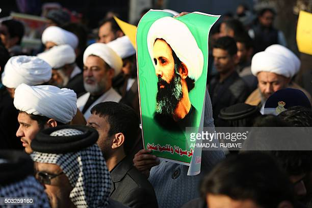 Iraqi Shiite clerics one holding a portrait of prominent Shiite Muslim cleric Nimr alNimr take part in a demonstration against his execution by Saudi...