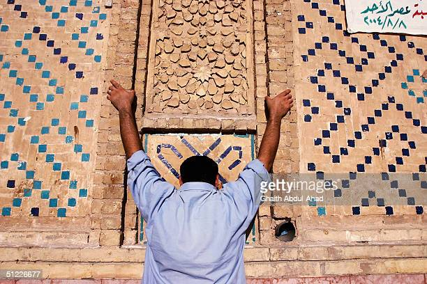 Iraqi Shiite faithfuls cry in front of the shrine of Imam Ali in Najaf today August 27 2004 after rebel leader Moqtada alSadr ordered his fighters to...