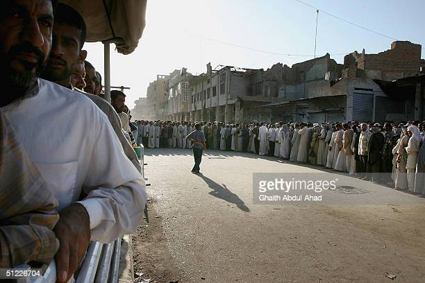Iraqi Shiite faithfuls queue outside the shrine of Imam Ali in Najaf today August 27 today August 27 2004 to mark the end of conlict The rebel leader...