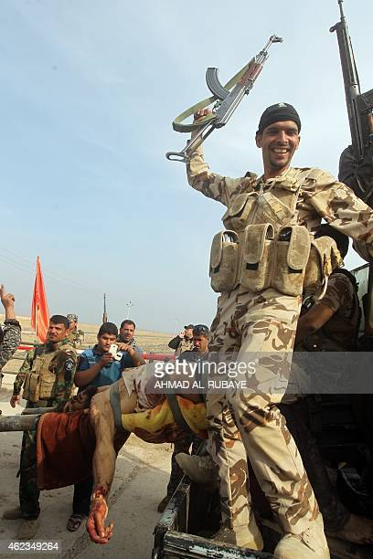 Iraqi Shiite fighters celebrate as they carry the body of a man reportedly a member of the Islamic State group after he was killed in the town of...