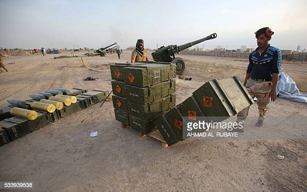 Iraqi Shiite fighters from a Popular Mobilisation unit carry boxes of ammunition near the city of Fallujah on May 23 as part of a major assault to...