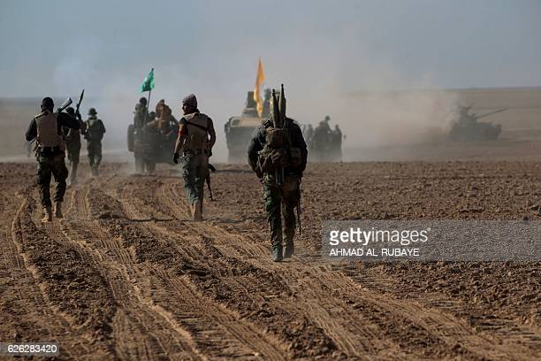 Iraqi Shiite fighters from the Hashed alShaabi paramilitaries advance in a desert area near the village of Tall Abtah southwest of Mosul on November...