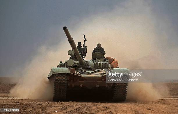 TOPSHOT Iraqi Shiite fighters from the Hashed alShaabi paramilitaries drive a T72 tank as they advance near the town of Tal Abtah south of Tal Afar...