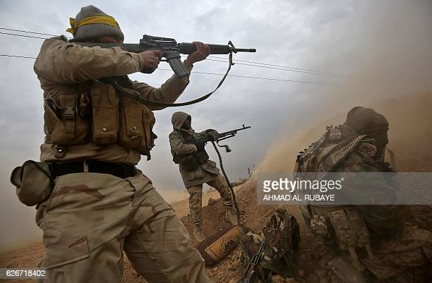 Iraqi Shiite fighters from the Hashed al-Shaabi paramilitaries fire their weapons as they advance near the town of Tal Abtah, south of Tal Afar, on...