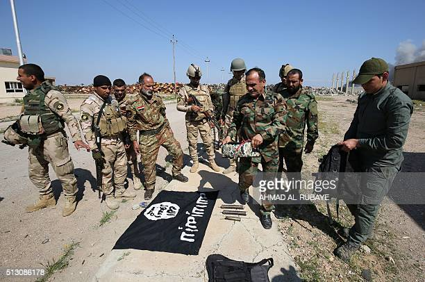 Iraqi Shiite fighters from the Popular Mobilisation units and Iraqi soldiers put an Islamic State group flag on the ground at an army position where...
