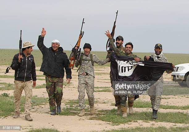 Iraqi Shiite fighters from the Popular Mobilisation units carry an Islamic State group flag on March 3 during an operation in the desert of Samarra...