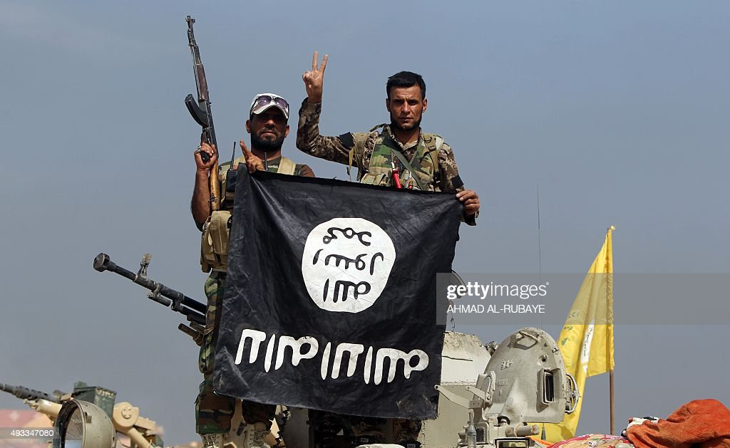Iraqi Shiite fighters from the Popular Mobilisation units, fighting alongside Iraqi government forces, display, upside down, the flag of the Islamic State (IS) group during a military operation aimed at the centre of Baiji, some 200 kilometres north of Baghdad on October 19, 2015. Iraqi forces advanced on three fronts against the Islamic State group, flushing out pockets of resistance in and around Baiji and closing in on Ramadi and Hawijah, officers said.