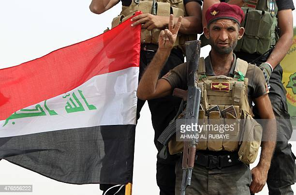 Iraqi Shiite fighters from the Popular Mobilisation units flash the 'V' for victory sign in the town of Baiji north of Tikrit as they fight alongside...