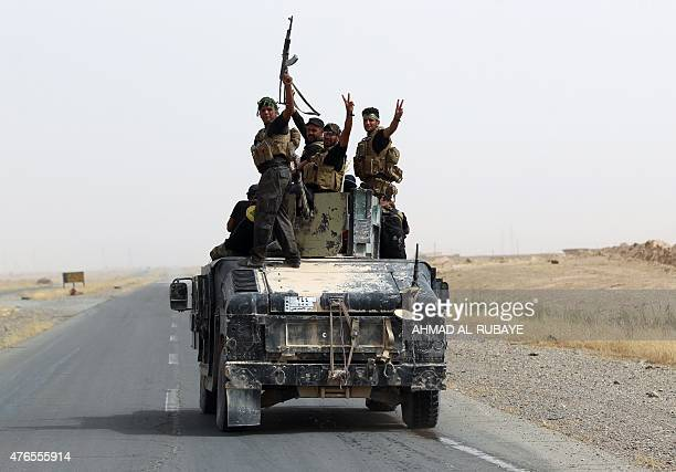 Iraqi Shiite fighters from the Popular Mobilisation units ride on a military Hummer in the town of Baiji north of Tikrit as they fight alongside...