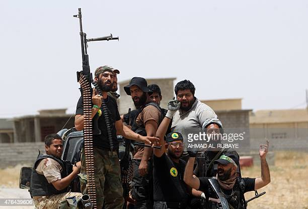 Iraqi Shiite fighters from the Popular Mobilisation units ride on the back of a vehicle in the city of Baiji north of Tikrit as they fight alongside...