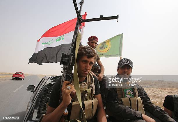 Iraqi Shiite fighters from the Popular Mobilisation units ride on the back of a vehicle in the town of Baiji north of Tikrit as they fight alongside...