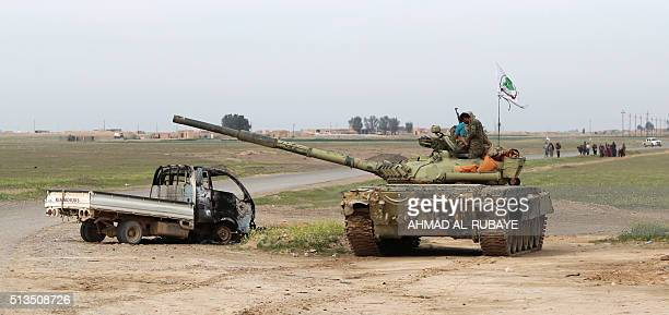 Iraqi Shiite fighters from the Popular Mobilisation units stand on a tank in the desert of Samarra on March 3 during an operation aimed at retaking...