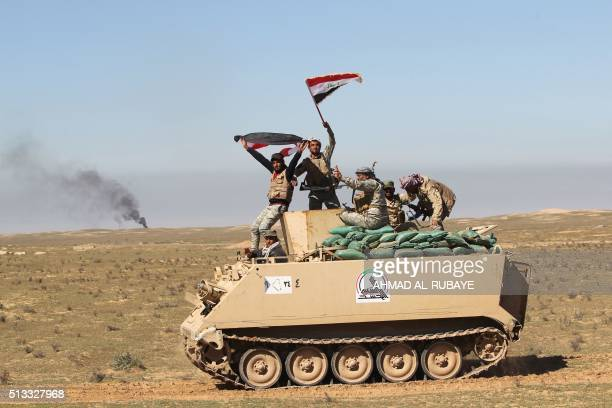 Iraqi Shiite fighters from the Popular Mobilisation wave their national flags as they drive down a road in the desert of Samarra on March 2 during an...