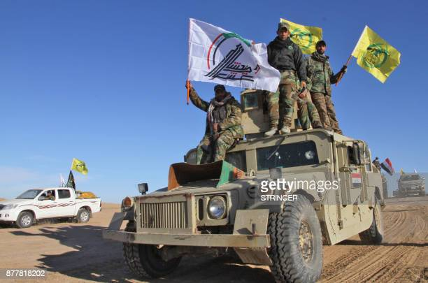Iraqi Shiite fighters of Saraya Ashura from the Hashed al-Shaabi wave their flags as they ride on a humvee as they advance with the Iraqi forces in...