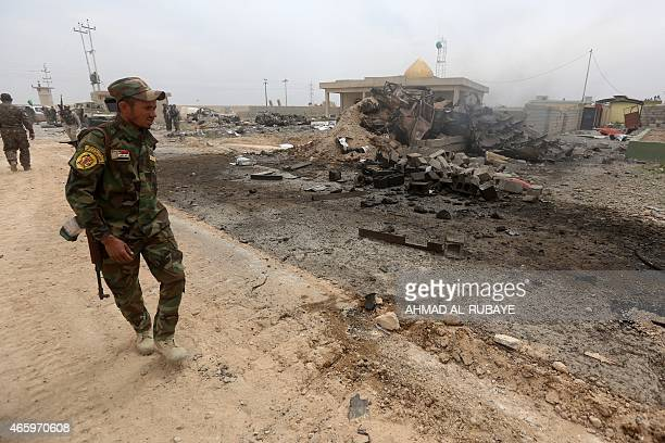 Iraqi Shiite fighters of the governmentcontrolled Popular Mobilisation units stand at the site of a car bomb that targeted progovernment forces on...