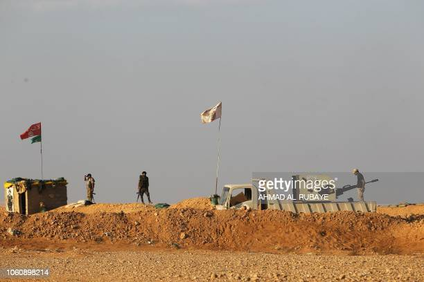 Iraqi Shiite fighters of the Hashed alShaabi paramilitary force secure the border area with Syria in alQaim in Iraq's Anbar province opposite Albu...
