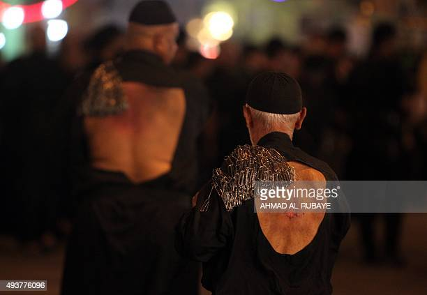 Iraqi Shiite men beat themselves with chains as part of a selfflagellation ritual during a parade in preparation for the peak of the mourning period...