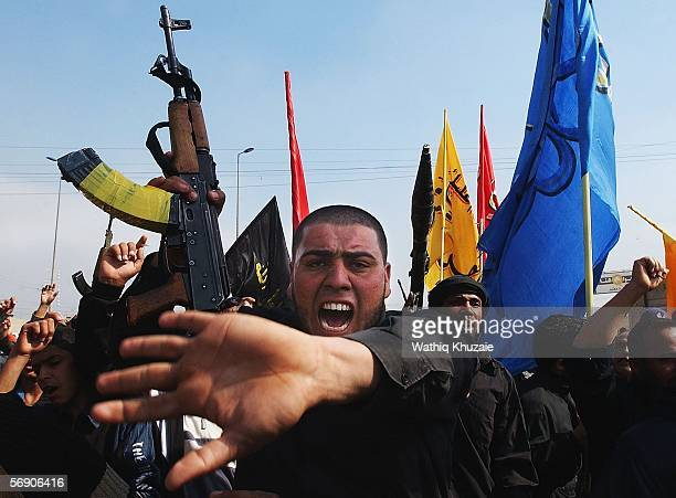 Iraqi Shiite men brandish their weapons and chant slogans as they protest the bombing of a Shiite holy shrine on February 22, 2006 in the Sadr city...