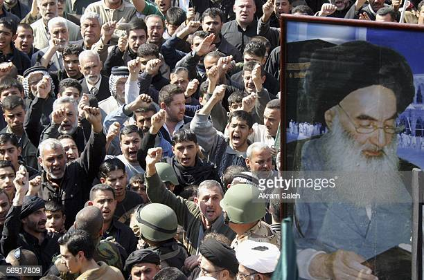 Iraqi Shiite men chant slogans as a picture of Iraq's powerful Shiite cleric Grand Ayatollah Ali al-Sistani is seen during a protest against the...