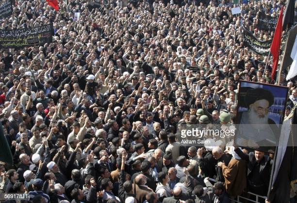 Iraqi Shiite men chant slogans as a picture of Iraq's powerful Shiite cleric Grand Ayatollah Ali alSistani is seen during a protest against the...