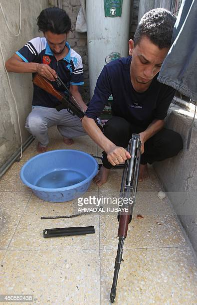 Iraqi Shiite men clean weapons as they get ready to defend their Sadr City district in case of an attack by Sunni extremists on June 13 2014 in...