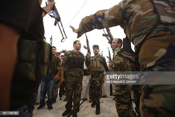 Iraqi Shiite men hold up their weapons during a training session in the shrine city of Karbala in central Iraq on June 25 2014 after they volunteered...