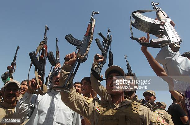 Iraqi Shiite men, some of them wearing military fatigues and guns given by the government, raise their weapons as they gather in the Iraqi town of...