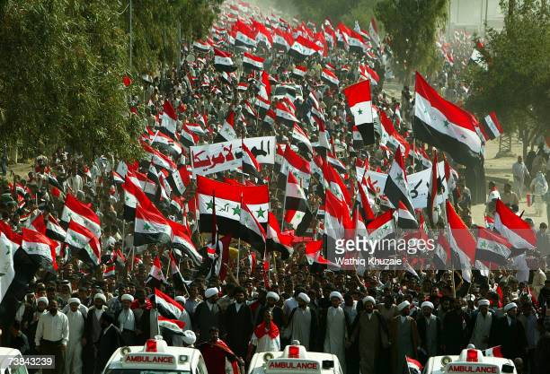 Iraqi Shiite men wave Iraqi flags during an antiUS protest called by firebrand Shiite cleric Moqtada alSadr to mark the fourth anniversary of the...